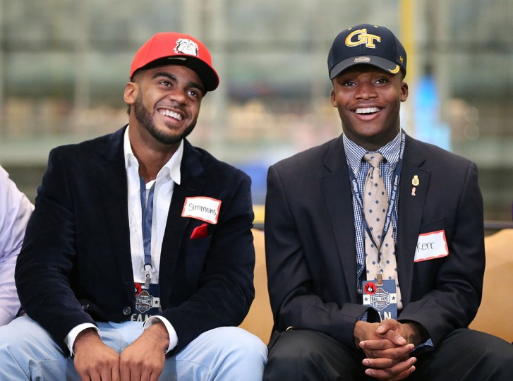 McEachern High School wide receiver Tyler Simmons, left, who flipped from Alabama to Georgia, laughs alongside teammate cornerback Ajani Kerr, who is going to in state rival Georgia Tech during national signing day at the College Football Hall of Fame, Wednesday, Feb. 3, 2016, in Atlanta. (Curtis Compton/Atlanta Journal-Constitution via AP)