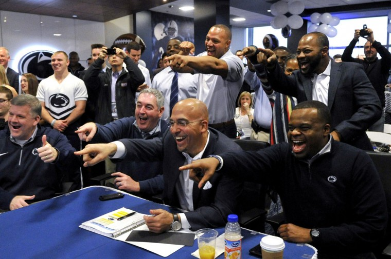 Penn State football head coach James Franklin, center, offensive coordinator Joe Moorhead, left, and coach Charles Huff, right, as well as coaches Josh Gattis, top center, and Terry Smith, top right, point and celebrate as they see recruit Miles Sanders on their screen during national signing day, Wednesday, Feb. 3, 2016, in State College, Pa. (Nabil K. Mark/Centre Daily Times via AP)