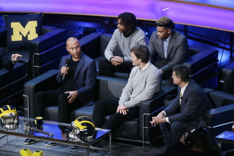 Derek Jeter, left, talks with former Michigan quarterback Tom Brady and Michigan football coach Jim Harbaugh, right, as new recruits Kingston Davis, top right, and Ahmir Mitchell listen in, during the Signing With the Stars spectacle, Wednesday, Feb. 3, 2016 in Ann Arbor, Mich. (AP Photo/Carlos Osorio)