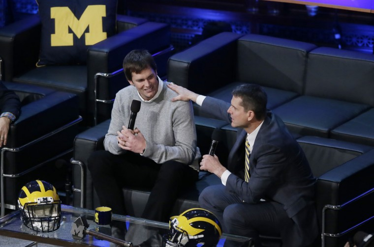 Michigan football coach Jim Harbaugh, right, talks with former school quarterback Tom Brady during the Signing With the Stars spectacle, Wednesday, Feb. 3, 2016 in Ann Arbor, Mich. College football's recruiting circus has found its ringmaster in Michigan's coach. Harbaugh was the real star of the Wolverines show that former coach Lou Holtz predicted will be copied in years to come by other schools. (AP Photo/Carlos Osorio)
