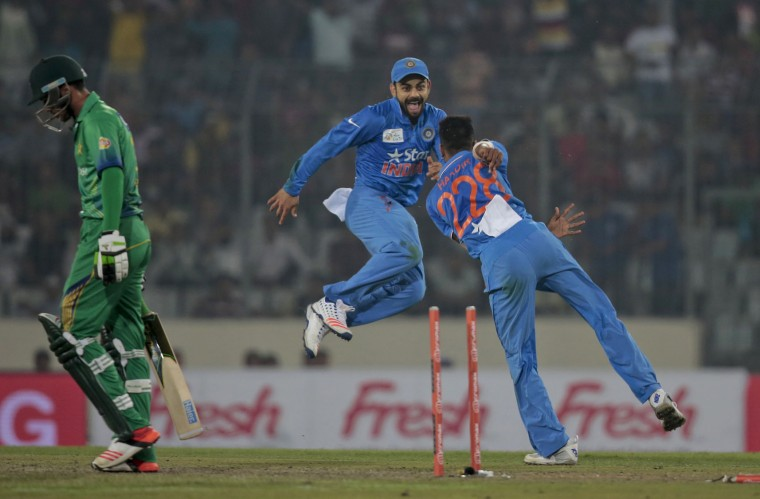 India''s Hardik Pandya, right, celebrates with his teammate Virat Kohli, center, after the dismissal of Pakistan''s Mohammad Amir, left, during their Asia Cup Twenty20 international cricket match in Dhaka, Bangladesh, Saturday, Feb. 27, 2016. (AP Photo/A.M. Ahad)