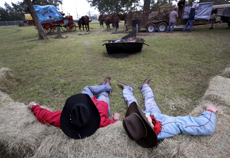 Billy Pope, left, and Zane Brown rest after a day of riding Tuesday, Feb. 23, 2016, in Tomball, Texas. They are part of the Sam Houston Trail Riders riding from Montgomery, Texas, to Houston. They will join more than 3,000 riders from all directions, including Louisiana and Mexico, for the Houston Livestock Show and Rodeo Downtown parade on Saturday in Houston. (AP Photo/David J. Phillip)
