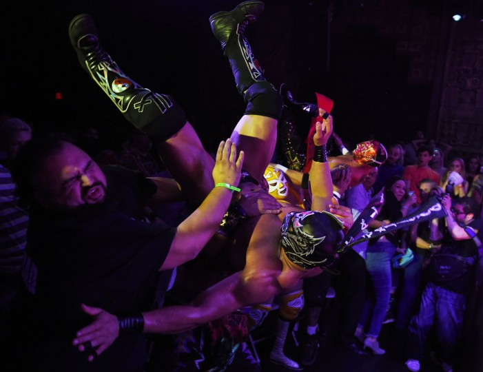 """Wrestlers Dragon Lee and Rey Horus hit the crowd after leaping towards their opponents during the Lucha Va Voom's """"Crazy in Love"""" show at the Mayan Theatre in downtown Los Angeles, California, on February 10, 2016. (MARK RALSTON/AFP/Getty Images)"""