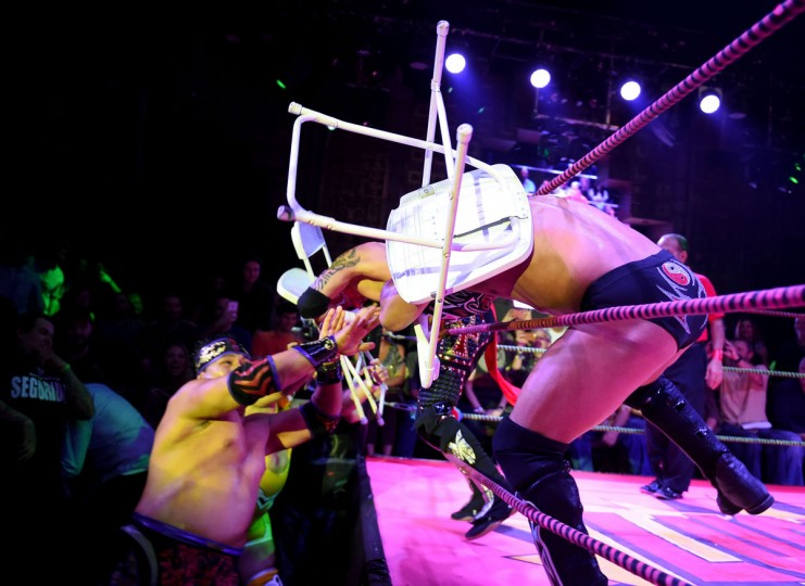 """Wrestler Rey Escorpian (left) hits Dragon Lee with a chair during the Lucha Va Voom's """"Crazy in Love"""" show at the Mayan Theatre in downtown Los Angeles, California on February 10, 2016. (MARK RALSTON/AFP/Getty Images)"""