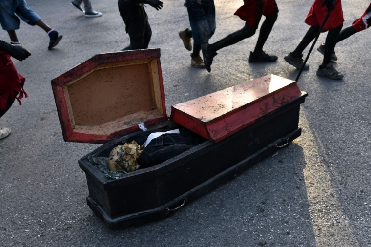 Revelers with bodies painted in motor oil depicting the devil run around a coffin during the 2016 National Carnival Parade on February 9, 2016 in Port-au-Prince, Haiti. (HECTOR RETAMAL/AFP/Getty Images)
