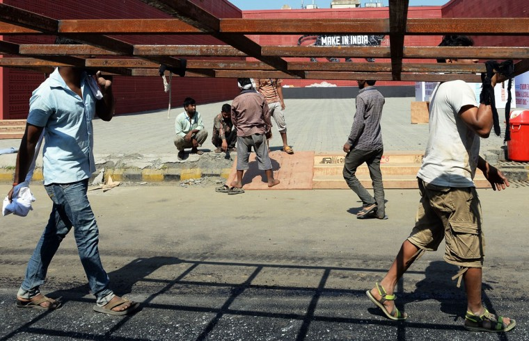Indian workers carry scaffolding at the venue for the 'Make in India' showcase week in Mumbai on February 11, 2016. (INDRANIL MUKHERJEE/AFP/Getty Images)