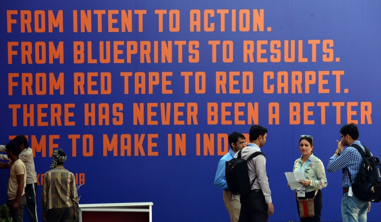 Exhibitors and staff interact in front of a slogan at the venue for the 'Make in India' showcase week in Mumbai on February 11, 2016. (INDRANIL MUKHERJEE/AFP/Getty Images)