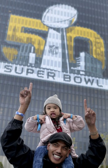 Sean Soliva and his daughter Kaylana, age 3, pose for a photo with a Super Bowl 50 sign at Super Bowl City Wednesday, Feb. 3, 2016, in San Francisco. (AP Photo/Charlie Riedel)