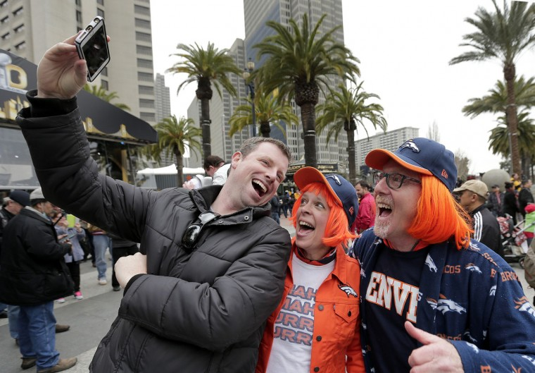 Denver Broncos fans Ted Cadigan, left, Sandy LaBelle and Daniel Oppenheim pose for a selfie at Super Bowl City Wednesday, Feb. 3, 2016, in San Francisco. (AP Photo/Charlie Riedel)
