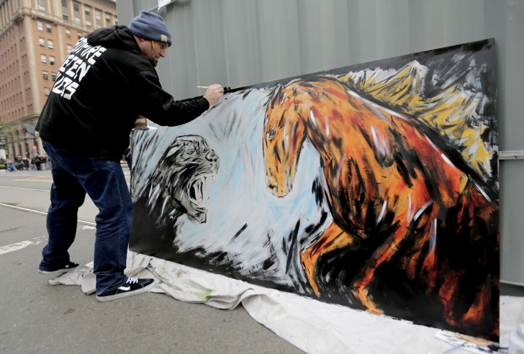 Kori Thompson works on a painting of a panther and a bronco at Super Bowl City Wednesday, Feb. 3, 2016, in San Francisco. (AP Photo/Charlie Riedel)