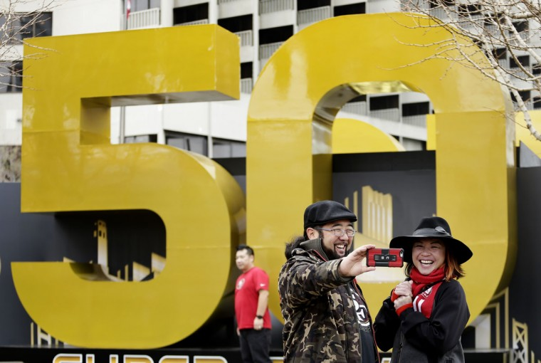 Carissa Lou and Marc Shimamoto pose for a selfie in front of a Super Bowl 50 sign at Super Bowl City Wednesday, Feb. 3, 2016, in San Francisco. (AP Photo/Charlie Riedel)