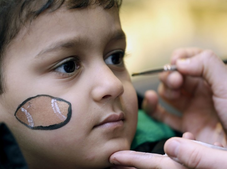 Kamron Samady, age 4, gets football images painted on his face at Super Bowl City Wednesday, Feb. 3, 2016, in San Francisco. (AP Photo/Charlie Riedel)