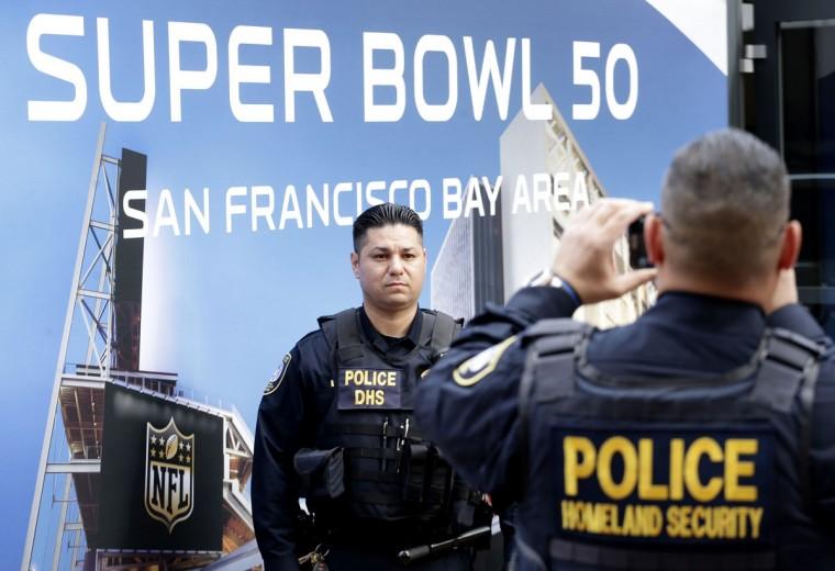 Law enforcement officers take photos of each other in front of Super Bowl 50 signs while providing security at Super Bowl City Wednesday, Feb. 3, 2016, in San Francisco. (AP Photo/Charlie Riedel)