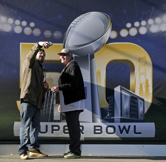 Josh Hatfield, left, takes a selfie with his dad Mark Hatfield at Super Bowl City Tuesday, Feb. 2, 2016 in San Francisco. The Denver Broncos play the Carolina Panthers in the NFL Super Bowl 50 football game Sunday, Feb. 7, 2015, in Santa Clara, Calif. (AP Photo/Charlie Riedel)
