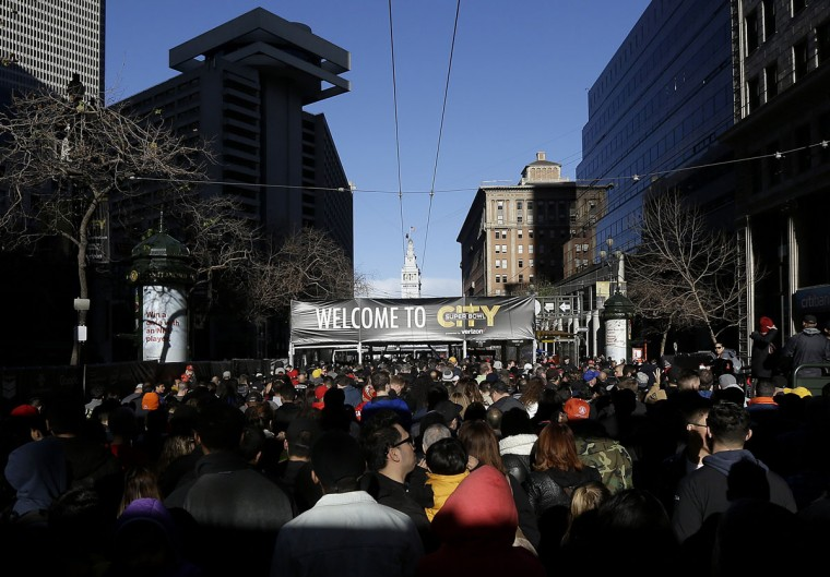 A crowd walks toward an entrance to Super Bowl City in San Francisco, Sunday, Jan. 31, 2016. The Denver Broncos will play the Carolina Panthers in Super Bowl 50 Sunday, Feb. 7, 2016. (AP Photo/Jeff Chiu)