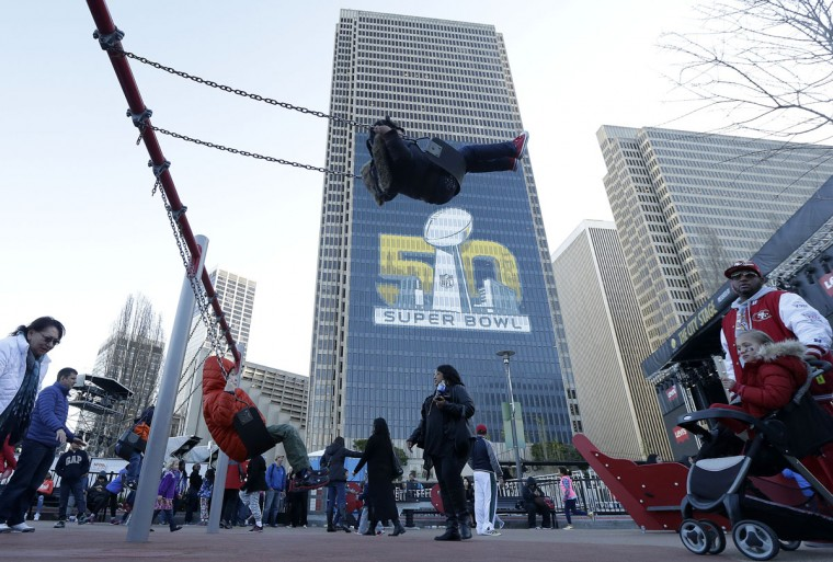 Cheyenne Dozier, 4, center, rides a swing at Sue Bierman Park Playground inside Super Bowl City in San Francisco, Sunday, Jan. 31, 2016. The Denver Broncos will play the Carolina Panthers in Super Bowl 50 Sunday, Feb. 7, 2016. (AP Photo/Jeff Chiu)