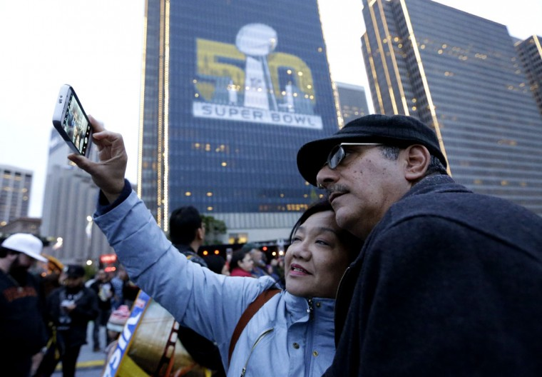 Lou and Evelyn Sarmiento take a selfie at Super Bowl City Saturday, Jan. 30, 2016, in San Francisco. The Denver Broncos will play the Carolina Panthers in Super Bowl 50 Sunday, Feb. 7, 2016. (AP Photo/David J. Phillip)