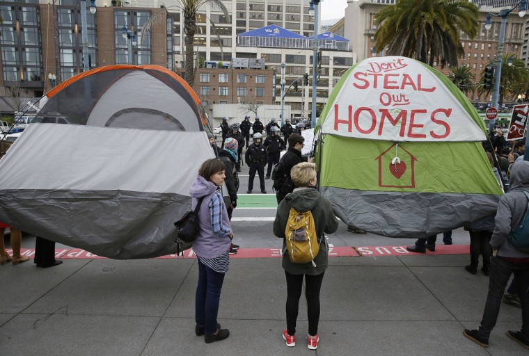 Demonstrators hold up tents during a protest to demand city officials do more to help homeless people outside Super Bowl City, a pro-football's weeklong theme park near the famed Ferry Building in San Francisco on Wednesday, Feb. 3, 2016. Dozens protested what they say is San Francisco Mayor Ed Lee's plan to push homeless people out of the scenic bay-front Embarcadero, where Super Bowl festivities are being held. (AP Photo/Eric Risberg)
