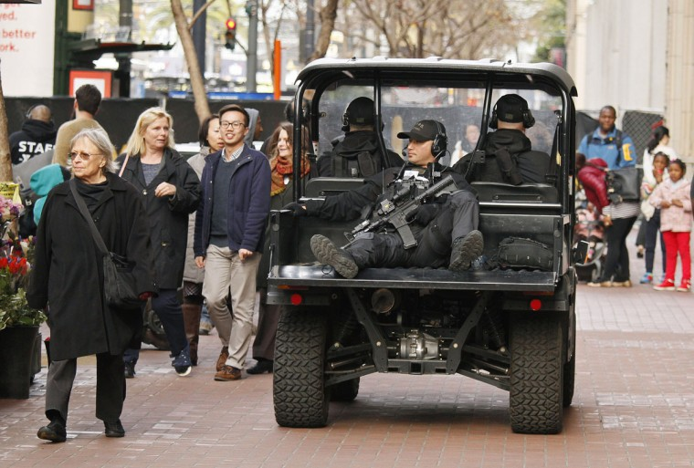 A San Francisco police officer rides in the back of a cart on Market Street outside Super Bowl City, a pro-football's weeklong theme park near the famed Ferry Building on The Embarcadero in San Francisco on Wednesday, Feb. 3, 2016. Super Bowl City is a free-to-the-public fan village to celebrate Super Bowl 50. (AP Photo/Eric Risberg)