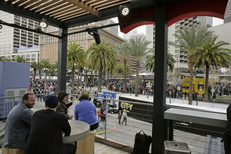 People sit in the Levi's rooftop bar and look out at Super Bowl City, a pro-football's weeklong theme park near the famed Ferry Building on The Embarcadero in San Francisco on Wednesday, Feb. 3, 2016. Super Bowl City is a free-to-the-public fan village to celebrate Super Bowl 50. (AP Photo/Eric Risberg)