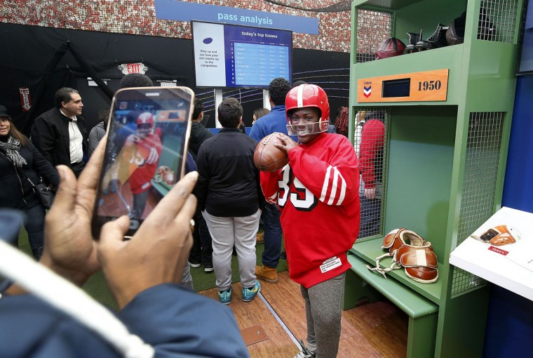 A student from Lavonya DeJean Middle School in Richmond, Calif., poses for a photo as she tries on helmets from past and present, to see how science has been a game changer for football in the Chevron STEM Zone in Super Bowl City on Tuesday, Feb. 2, 2016 in San Francisco. The Chevron STEM Zone is an interactive exhibit that brings the science behind football to life for fans in Super Bowl City. (Tony Avelar/AP Images for Chevron)