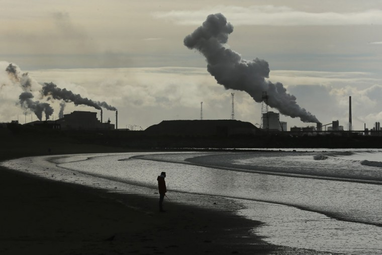 A man walks his dog on Aberavon beach in the shadow of the Tata Steel plant at Port Talbot on March 30, 2016 in Port Talbot, Wales. Indian owners Tata Steel put its British business up for sale yesterday, placing thousands of jobs at risk and hitting the already floundering UK steel industry. (Photo by Christopher Furlong/Getty Images)