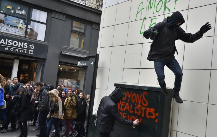People tag a wall as thousands of people demonstrate on March 9, 2016 in Nantes, western France, as part a nationwide day of protest against proposed labour reforms. France faced a wave of protests against deeply unpopular labour reforms that have divided an already-fractured Socialist government and raised hackles in a country accustomed to iron-clad job security. (AFP / Loic Venance)