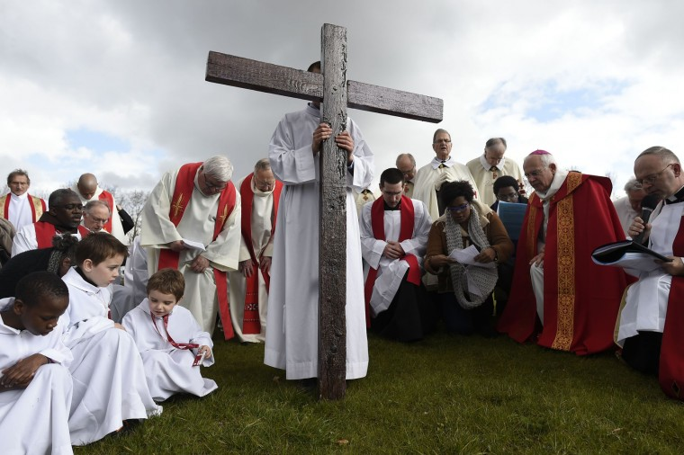 People walk behind a wooden cross as part of a Good Friday procession towards the Saint-Denys Basilica where the Holy Tunic of Argenteuil, believed to have been worn by Jesus, is displayed on March 25, 2016. (Lionel Bonaventure/AFP/Getty Images)