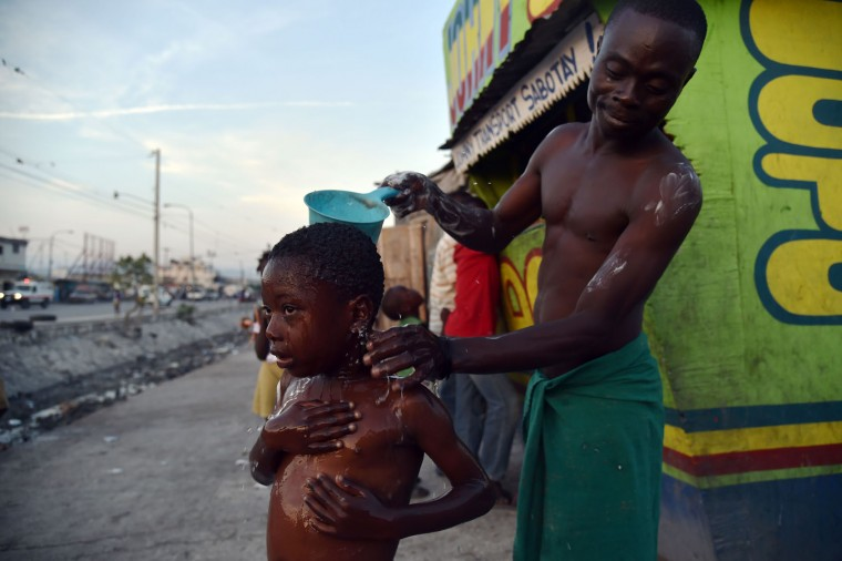 Beloni (34) gives a bath to his son, 6, on a small street in the neighborhood of Cite Vincent, on March 21, 2016, commune of Cite Soleil in the Haitian capital Port-au-Prince. World Water Day, marked on March 22, 2016, is an international observance to learn more about water related issues and to take action for sustainable management of freshwater resources. (Hector Retamal/AFP/Getty Images)