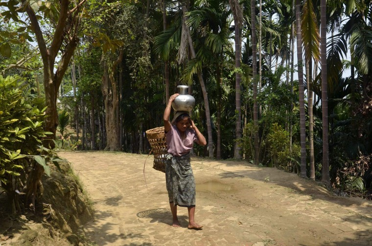 An Indian tribal woman carries water from a rivulet, in a jug on her head for drinking, during World Water Day in Baramura Hills on the outskirts of Agartala, capital of the northeastern state of Tripura, on March 22, 2016. (Arindam Dey/AFP/Getty Images)