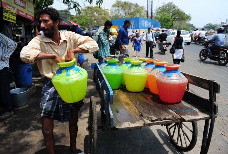 An Indian man carries a pot containing drinking water from his suppy cart water supply tanker at a commercial area in Chennai on March 22, 2016. International World Water Day is marked annually on March 22 to focus global attention on the importance of water and advocate for sustainable water resource management. (Arun Sankar/AFP/Getty Images)