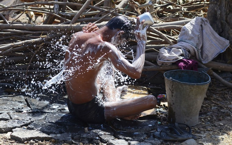 An Indian man take a bath after collecting water from a road side tap in Allahabad on March 22, 2016. International World Water Day is held annually on March 22 to focus global attention on the importance of water and advocating for the sustainable management of our water resources. (Sanjay Kanojia/AFP/Getty Images)