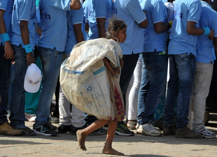 An Indian child carries a sack to collect used water bottles as school students take part in an awareness rally held to mark World Water Day in Hyderabad on March 22, 2016. The United Nations World Water Day is marked anually on March 22 and in 2016 focuses on the positive impact water quantity and quality can have on workers lives and livelihoods, and societies and economies. (Noah Seelam/AFP/Getty Images)