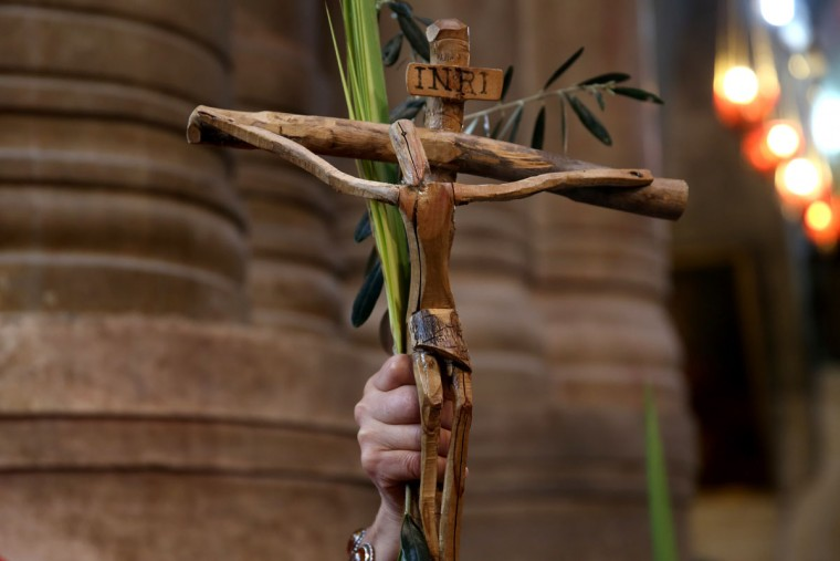 A Catholic pilgrim holds up a crucifix and a palm branch during the Palm Sunday procession at the Church of the Holy Sepulchre in Jerusalem's Old City on March 20, 2016. The ceremony is a landmark in the Roman Catholic calendar, marking the triumphant return of Christ to Jerusalem the week before his death, when a cheering crowd greeted him waving palm leaves. Palm Sunday marks the start of the most solemn week in the Christian calendar. (AFP PHOTO / GALI TIBBON)
