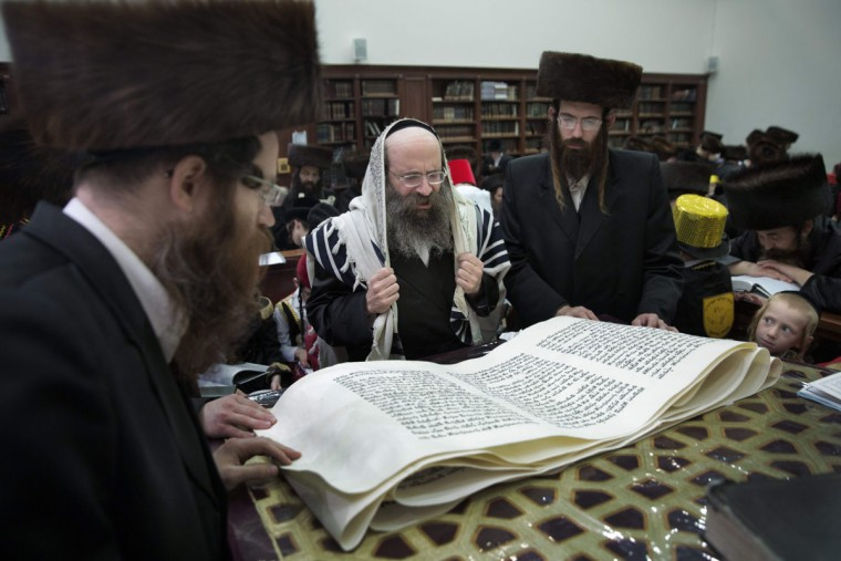Ultra-Orthodox Jewish men read the book of Esther at a synagogue in the Israeli city of Beit Shemesh on March 23, 2016 during the feast of Purim. The carnival-like Purim holiday is celebrated with parades and costume parties to commemorate the deliverance of the Jewish people from a plot to exterminate them in the ancient Persian empire 2,500 years ago, as recorded in the Biblical Book of Esther. (AFP Photo/Menahem Kahana)