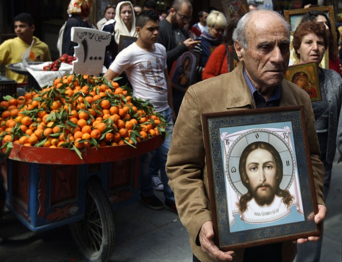 A Greek Orthodox Christian man holds an icon depicting Jesus Christ as he walks with Christian Melkites during a joint procession in the streets of the southern Lebanese city of Sidon on March 20, 2016, to mark Palm Sunday, which commemorates the triumphal entry of Jesus into Jerusalem one week before His Passion, Death, and Resurrection. The Melkite also known as the Greek Catholic Church traces its origins to the Christian communities of the Levant and Egypt. (AFP PHOTO / Patrick BAZ)