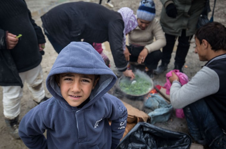 A Syrian boy looks at the camera as people cook outside at the Idomeni refugee camp on the Greek Macedonia border on March 16, 2016 in Idomeni, Greece. The decision by Macedonia to close its border to migrants last week has left thousands of people stranded at the Greek transit camp. The closure, following the lead taken by neighbouring countries, has effectively sealed the so-called western Balkan route, the main migration route that has been used by hundreds of thousands of migrants to reach countries in western Europe such as Germany. Humanitarian workers have described the conditions at the camp as desperate, which has been made much worse by recent spells of heavy rain. (Photo by Matt Cardy/Getty Images)
