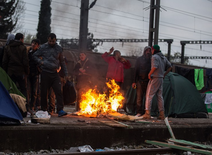 Men gather around a fire at the railway station at the Idomeni refugee camp on the Greek Macedonia border on March 16, 2016 in Idomeni, Greece. The decision by Macedonia to close its border to migrants last week has left thousands of people stranded at the Greek transit camp. The closure, following the lead taken by neighbouring countries, has effectively sealed the so-called western Balkan route, the main migration route that has been used by hundreds of thousands of migrants to reach countries in western Europe such as Germany. Humanitarian workers have described the conditions at the camp as desperate, which has been made much worse by recent spells of heavy rain. (Photo by Matt Cardy/Getty Images)