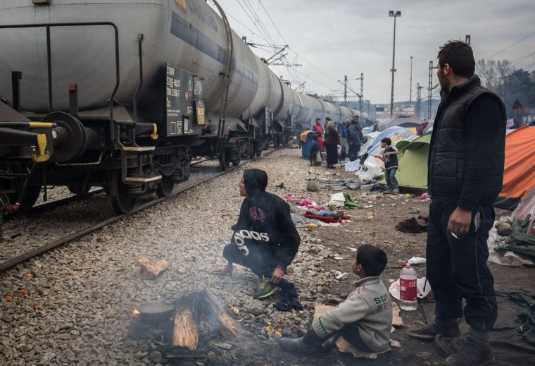 People sit besides a fire as a train passes at the Idomeni refugee camp on the Greek Macedonia border on March 16, 2016 in Idomeni, Greece. The decision by Macedonia to close its border to migrants last week has left thousands of people stranded at the Greek transit camp. The closure, following the lead taken by neighbouring countries, has effectively sealed the so-called western Balkan route, the main migration route that has been used by hundreds of thousands of migrants to reach countries in western Europe such as Germany. Humanitarian workers have described the conditions at the camp as desperate, which has been made much worse by recent spells of heavy rain. (Photo by Matt Cardy/Getty Images)