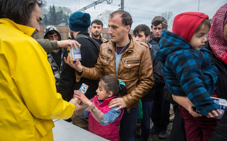 People receive food aid at the Idomeni refugee camp on the Greek Macedonia border on March 16, 2016 in Idomeni, Greece. The decision by Macedonia to close its border to migrants last week has left thousands of people stranded at the Greek transit camp. The closure, following the lead taken by neighbouring countries, has effectively sealed the so-called western Balkan route, the main migration route that has been used by hundreds of thousands of migrants to reach countries in western Europe such as Germany. Humanitarian workers have described the conditions at the camp as desperate, which has been made much worse by recent spells of heavy rain. (Photo by Matt Cardy/Getty Images)