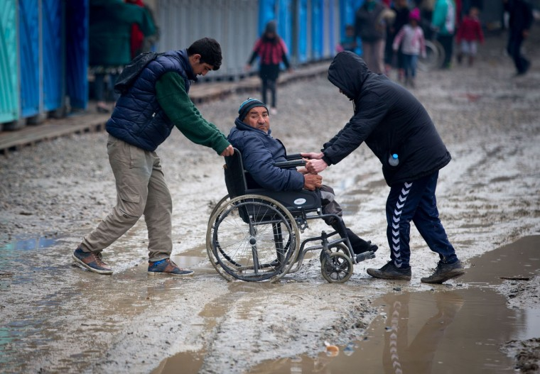 A man in a wheelchair is helped through the mud at the Idomeni refugee camp on the Greek Macedonia border on March 16, 2016 in Idomeni, Greece. The decision by Macedonia to close its border to migrants last week has left thousands of people stranded at the Greek transit camp. The closure, following the lead taken by neighbouring countries, has effectively sealed the so-called western Balkan route, the main migration route that has been used by hundreds of thousands of migrants to reach countries in western Europe such as Germany. Humanitarian workers have described the conditions at the camp as desperate, which has been made much worse by recent spells of heavy rain. (Photo by Matt Cardy/Getty Images)