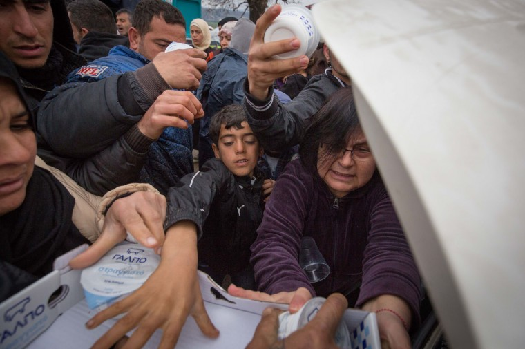 People scramble for supplies being delivered by car at the Idomeni refugee camp on the Greek Macedonia border on March 16, 2016 in Idomeni, Greece. The decision by Macedonia to close its border to migrants last week has left thousands of people stranded at the Greek transit camp. The closure, following the lead taken by neighbouring countries, has effectively sealed the so-called western Balkan route, the main migration route that has been used by hundreds of thousands of migrants to reach countries in western Europe such as Germany. Humanitarian workers have described the conditions at the camp as desperate, which has been made much worse by recent spells of heavy rain. (Photo by Matt Cardy/Getty Images)