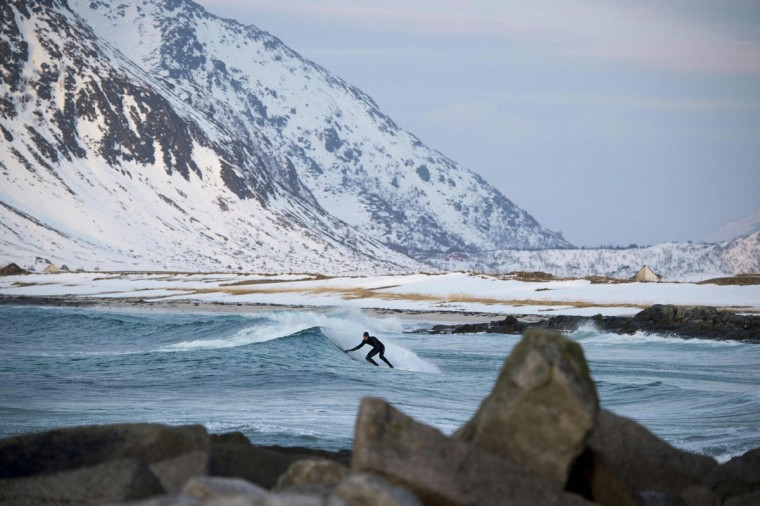 A surfer rides a wave at the snowy beach of Flackstad, near Ramberg, in Lofoten archipelago, Arctic Circle, on March 12, 2016. Surfers from all over the world come to Lofoten islands to surf in extreme conditions. Ocean temperature is 5-6 °C, air temperature around 0°C in spite of a weather very unstable. (OLIVIER MORIN/AFP/Getty Images)