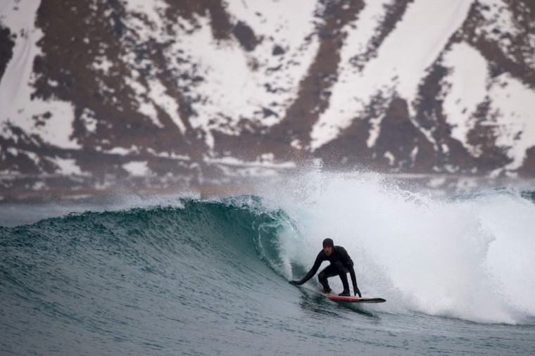 A surfer rides a wave at the snow covered beach of Flackstad, near Ramberg, on Lofoten Island, Arctic Circle, on March 12, 2016. Surfers from all over the world come to Lofoten island to surf in extreme conditions. Ocean temperature is 5-6 °C, air temperature around 0°C in spite of a weather very unstable. (OLIVIER MORIN/AFP/Getty Images)