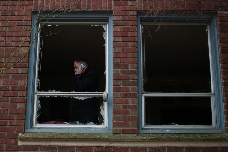 A man stands in his apartment with broken windows during the aftermath of a natural gas explosion destroyed businesses on Greenwood Avenue during the early morning hours on March 9, 2015 in Seattle, Washington. Nine firefighters who were battling the blaze were injured, but have since been released from Harborview Medical Center according to Seattle Fire Department. (Matt Mills McKnight/Getty Images)