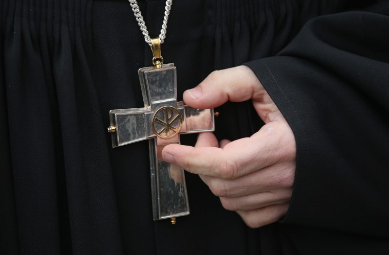 A Protestant pastor touches a cross hanging from his neck during a Good Friday procession on March 25, 2016 in Berlin, Germany. Christians across the globe will celebrate Easter throughout this weekend, including Good Friday, when according to Christian tradition Jesus Christ was crucified and died. (Photo by Sean Gallup/Getty Images)