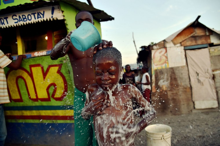 Beloni (34) gives a bath to his son, 6, on a small street in the neighborhood of Cite Vincent, on March 21, 2016 in the commune of Cite Soleil in the Haitian capital Port-au-Prince. World Water Day, marked on March 22, 2016, is an international observance to learn more about water related issues and to take action for sustainable management of freshwater resources. (Hector Retamal/AFP/Getty Images)