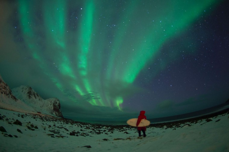A surfer stands by northern lights ( aurora borealis ) on the snow covered beach of Unstad, on Lofoten Island, Arctic Circle, on March 10, 2016. (OLIVIER MORIN/AFP/Getty Images)