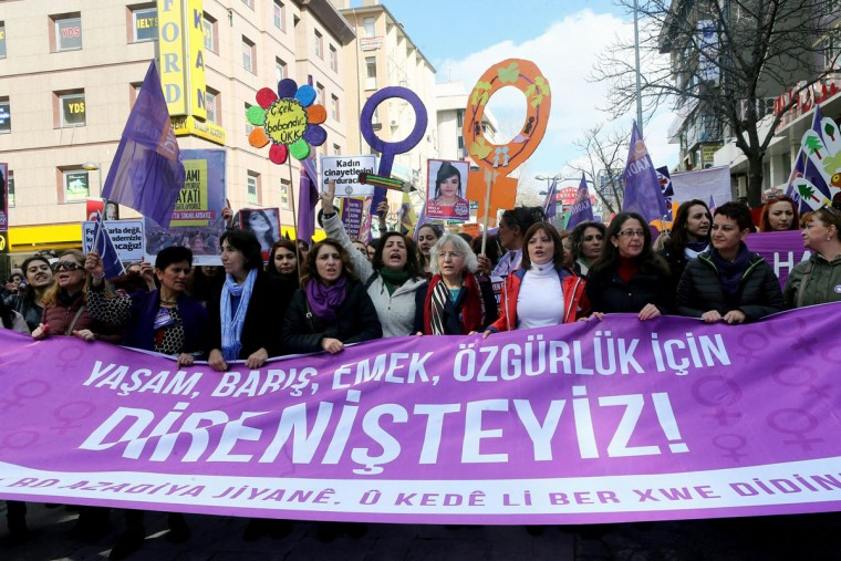 "Turkish women shout slogans as they carry a banner which translates as "" We resist for life, peace, labour and freedom."" during a demonstration marking International Women's Day in Ankara on March 6, 2016. (Adem Altan/AFP/Getty Images)"