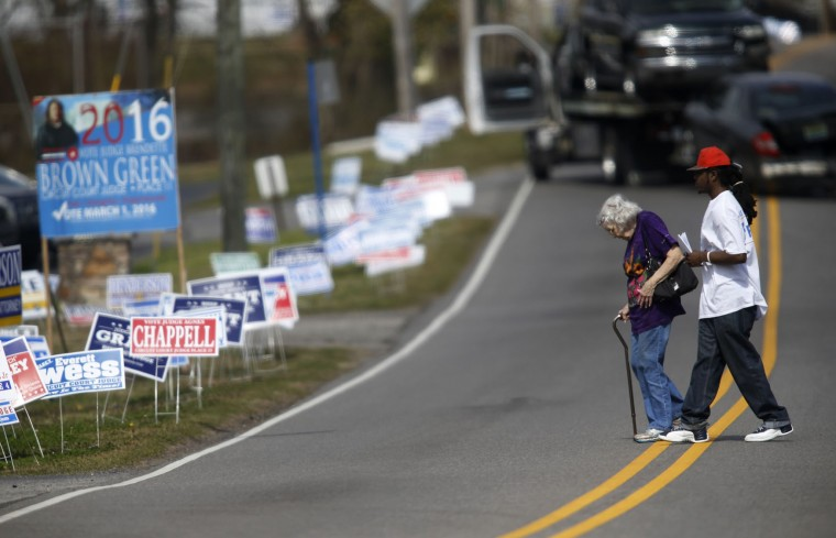 Sebastian Connor helps a voter cross the street to reach her polling place at Our Lady-Lourdes Catholic Church in Birmingham, Alabama. 13 states and American Samoa are holding presidential primary elections, with over 1400 delegates at stake. (Photo by Hal Yeager/Getty Images)
